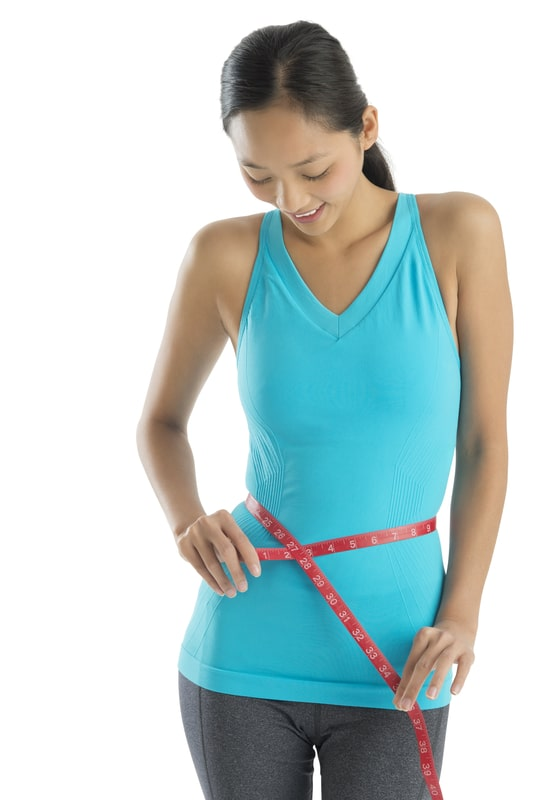 Woman In Sports Clothing Measuring Her Waist